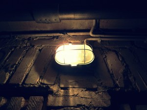 A photo of an exposed light bulb in a black wire cage on a brick wall in a basement