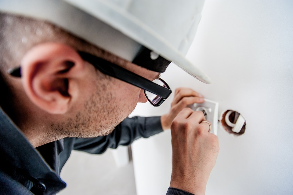 an image of a man fixing a plug