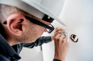 an imahe of a man wearing safety hat wiring a socket
