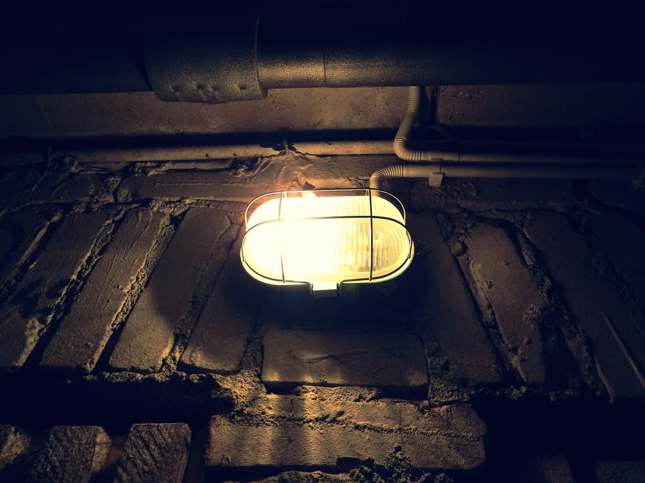 A photo of an exposed light bulb in a black wire cage on a brick wall.  Depending on where your fuse box ...