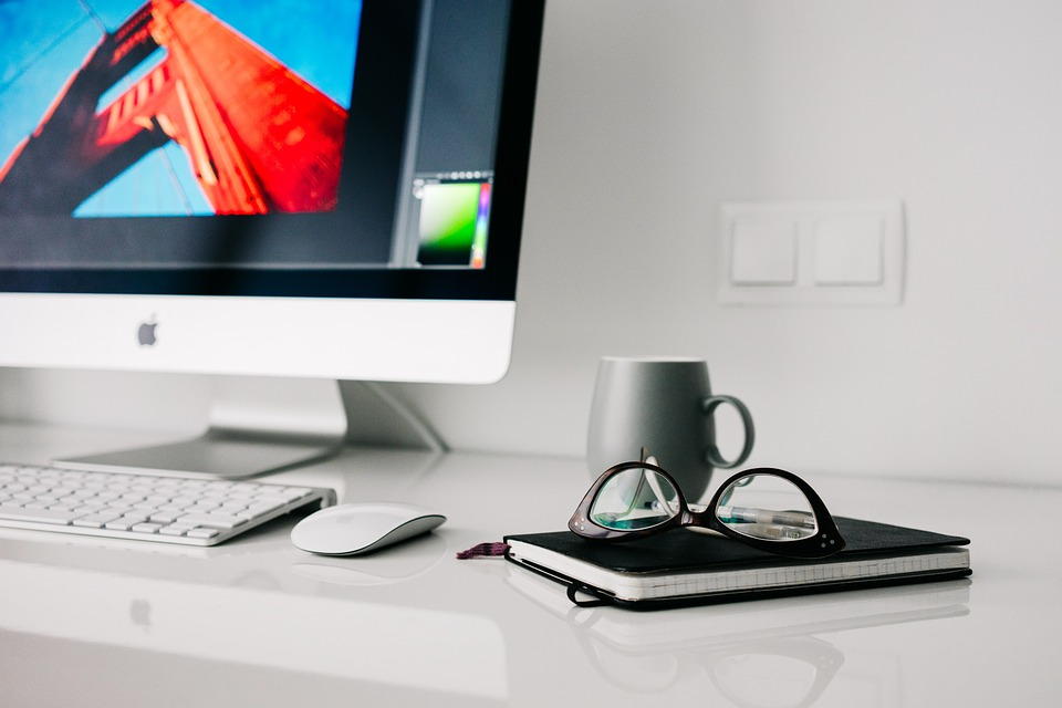 an image of a mac computer on a desk with a notebook, glasses and mug